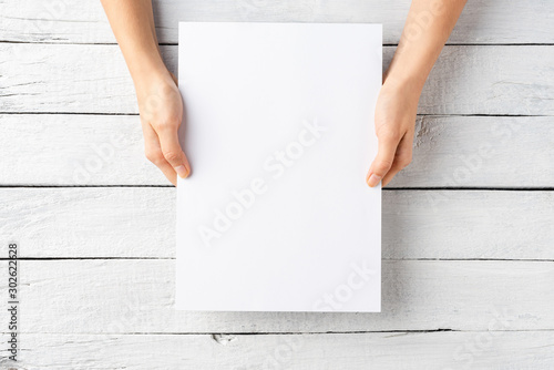 Young female hands holding paper sheet with copyspace. Top view Tablou Canvas