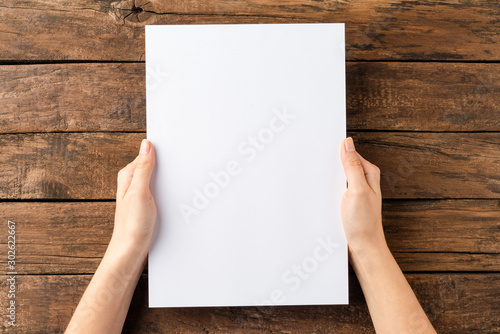Fototapeta Overhead shot of woman's hands holding blank paper sheet on rustic wooden table. Close up obraz