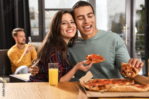 Fotomural  Young couple eating delicious pizza in cafe