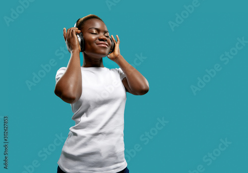 Relaxed female in bluetooth headphones listening music - 302627853