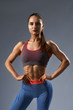 Front view of fitness brunette female with muscular body