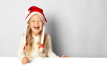 Portrait Of Little Pretty Girl Laughs In Santa Hat With Sale (advertising) Empty Blank. Holding Xmas Cardboard On White Background. Happy New Year.