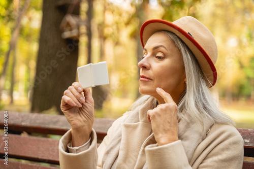Focused pretty female using a pocket mirror