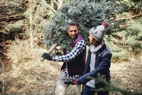 Father and son carrying fresh Christmas tree