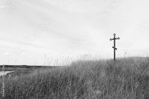 Deurstickers Grijs Black-and-white photo with wooden cross on sky background