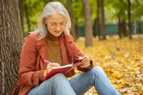 Smiling lady in eyeglasses writing in a park