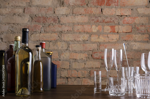 Foto auf Leinwand Alkohol Bar counter and bottle of drinks, glassware on it, vintage red brick wall.Empty space for text