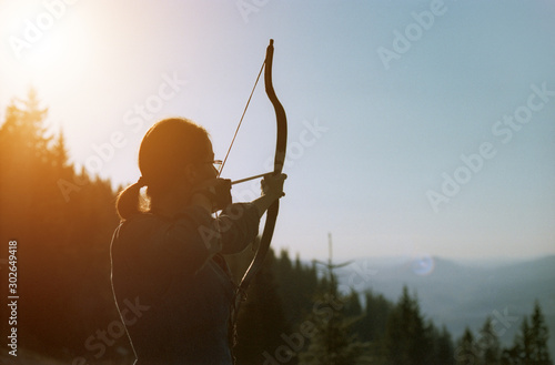Young Caucasian woman in an archer historical costume shooting with a bow in the mountains in summer Wallpaper Mural