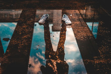 Creative Play With Reflections In A Puddle, Empty Shoes
