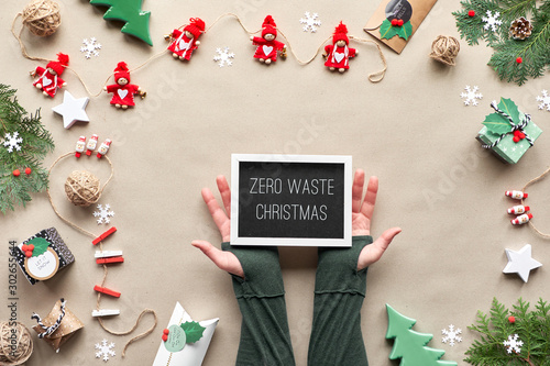 Fotomural  Zero waste Christmas, flat lay, top view on craft paper background with textile doll garland, wrapped gifts, black board with text Zero Waste Christmas on color paper