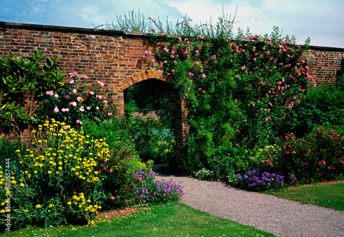 Cuadros en Lienzo A Walled garden with climbing roses and a flower border at a Country House