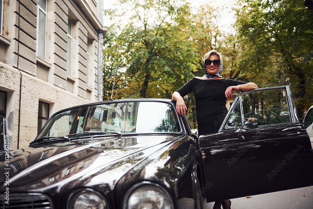 Fototapeta Blonde woman in sunglasses and in black dress near old vintage classic car