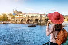 Elegante Touristin Mit Hut Schaut Auf Die Berühmte Karlsbrücke In Prag, Tschechien, An Einem Sonnigen Tag