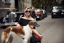 Blonde Woman In Sunglasses And In Black Dress Near Old Vintage Classic Car With Her Dog