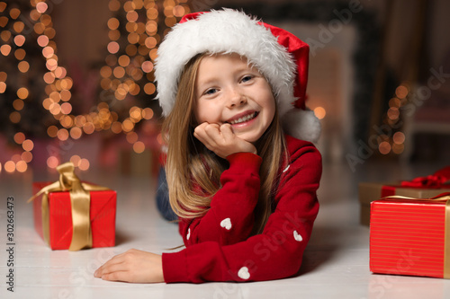 Cute little child with Christmas gifts at home