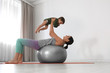 Young woman doing exercise with her son indoors. Home fitness