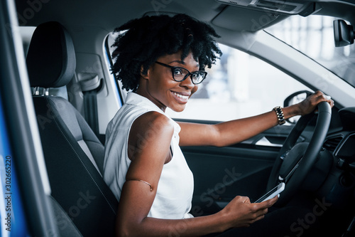 Obraz Using phone. Young african american woman sits inside of new modern car - fototapety do salonu