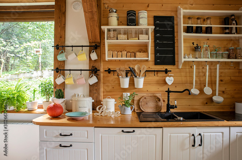 Obraz Interior of kitchen in rustic style with vintage kitchen ware and window. White furniture and wooden decor in bright indoor.	 - fototapety do salonu
