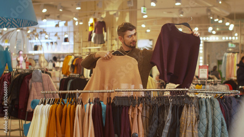 Guy is looking for a certain sweater in a store Canvas-taulu