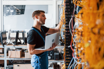 Young man in uniform and with laptop works with internet equipment and wires in server room