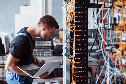 Obraz Young man in uniform and with laptop works with internet equipment and wires in server room - fototapety do salonu