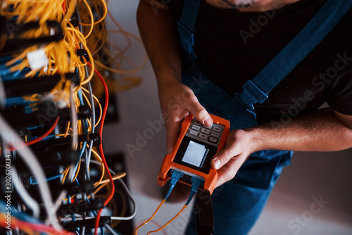 Fotografía  Top view of young man in uniform with measuring device that works with internet