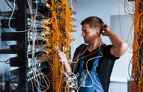 Young man in uniform feels confused and looking for a solution with internet equipment and wires in server room