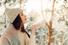 Girl In Pink Mittens Blows In The Snow In A Pine Forest On A Sunny Day