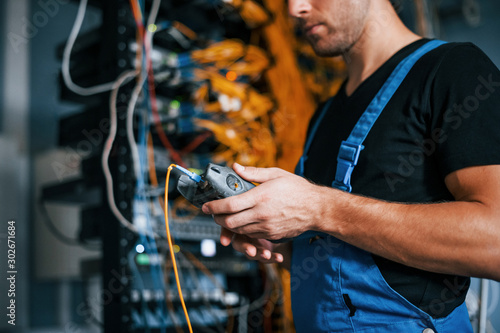 Young man in uniform have a job with internet equipment and wires in server room Fototapeta