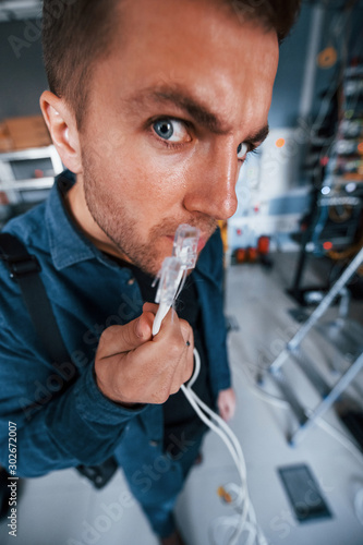 Canvas Close up view of funny man with internet wires in server room