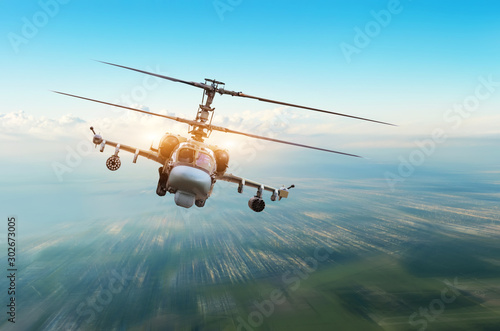 Photo Combat military helicopter with weapons flies over the city.