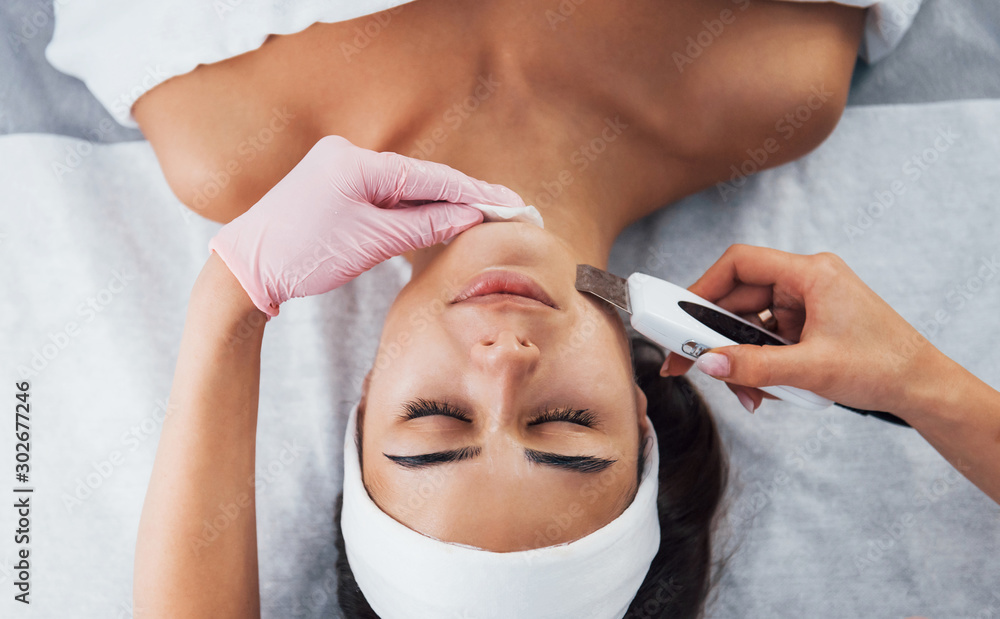 Fototapeta Using special device. Close up view of woman that lying down in spa salon and have face cleaning procedure