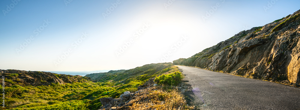 Fototapeta Empty long mountain road to the horizon on a sunny summer day at bright sunset