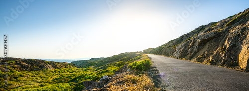 Fototapeta Empty long mountain road to the horizon on a sunny summer day at bright sunset obraz
