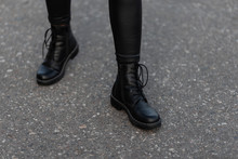 Modern Young Woman In Black Stylish Leggings In Fashionable Leather Boots Stands On The Road In The City. Trendy Collection Of Women's Autumn Shoes. Close Up Of Female Legs.