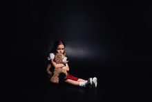 Lonely, Scared Kid Sitting On Floor And Hugging Teddy Bear On Black Background