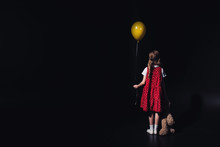 Back View Of Depressed Child With Yellow Balloon And Teddy Bear Isolated On Black