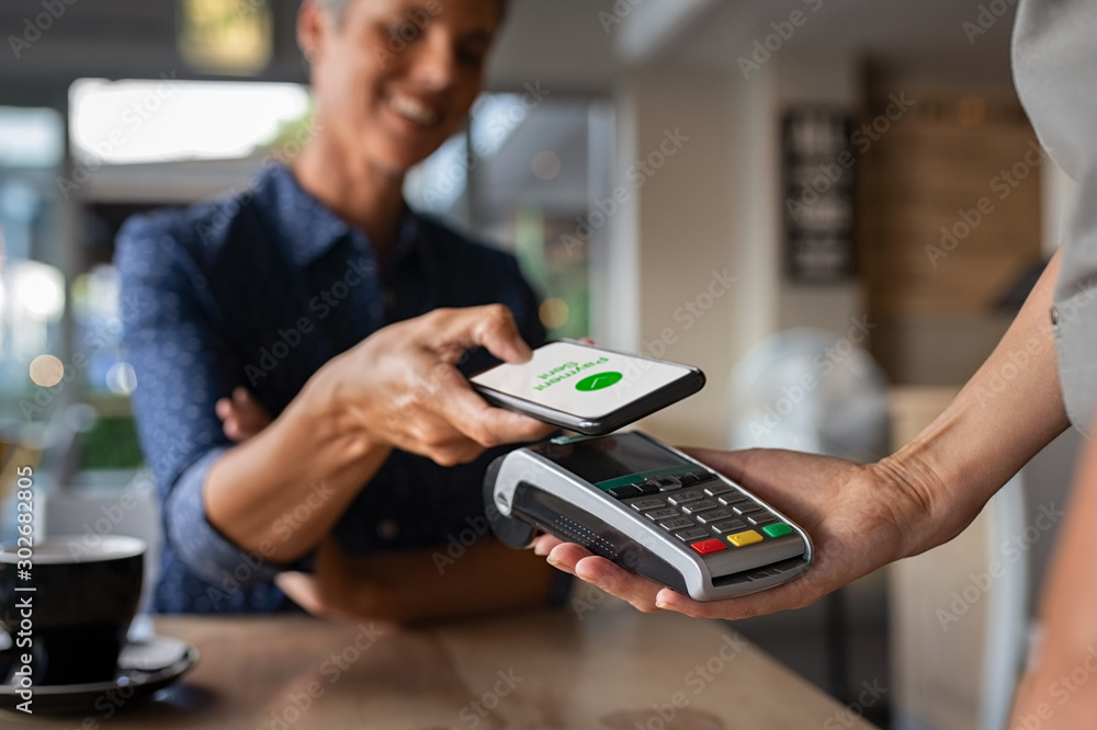 Fototapeta Woman paying using NFC technology