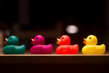 Four Plastic Ducks In Single File. The Ducks' Colors Are Green, Violet, Red And Yellow. Blur Background. Copy Space On Top. Concept Of Childhood, Have A Bath, Be A Little Child