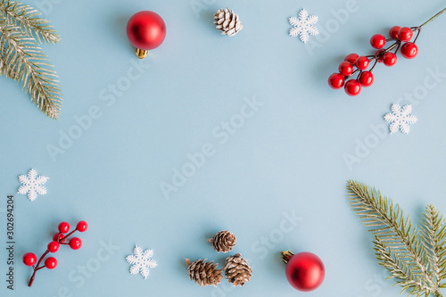 Obraz Christmas frame made of fir branches, red berries, snowflakes, bauble decoration and pine cones on blue background. Christmas background. Flat lay. Top view with copy space - fototapety do salonu