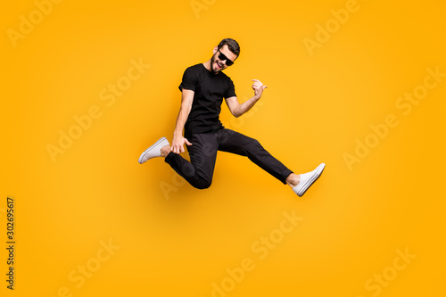 Fotografía Full body profile photo of crazy hipster guy jumping high holding imagine solo g