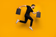 Full length photo of handsome millennial guy jumping high running shopping mall buying new clothes hold bags wear black t-shirt pants isolated yellow color background