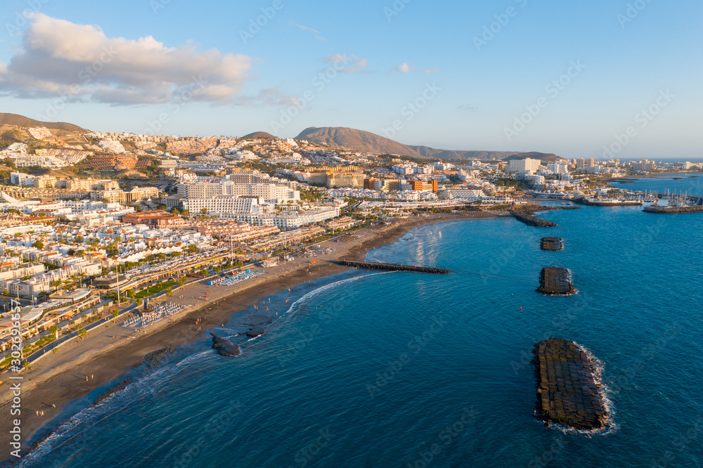 Fototapety, obrazy: Drone aerial shot of Costa Adeje area, South Tenerife, Spain. Captured at golden hour, warm and vivid sunset colors. Luxury hotels, villas and restaurants behind the beach.