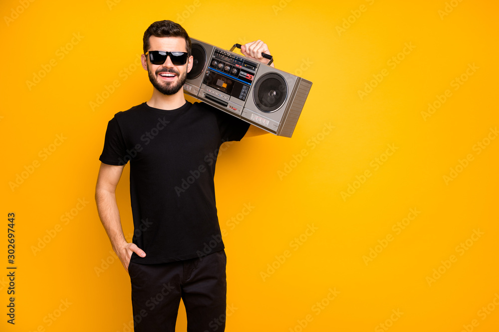 Fototapeta Portrait of cool charming positive guy hold boom box on his shoulder want listen vintage music on journey wear black friday clothes isolated over bright color background