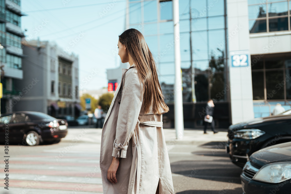 Fototapety, obrazy: A girl in a raincoat sadly wanders through the city among cars and buildings