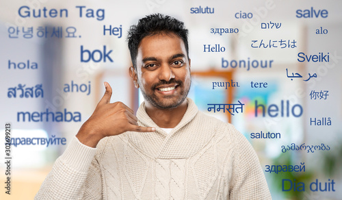 Keuken foto achterwand Dinosaurs emotion, expression and people concept - smiling indian man in knitted woolen sweater making phone call gesture over greeting words in different foreign languages