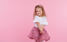 A Cheerful Little Girl With In A Tulle Skirt And Princess Crown On Her Head Isolated On A Pink Background. Celebrating A Vibrant Carnival For Kids, Birthday Party, Having Fun