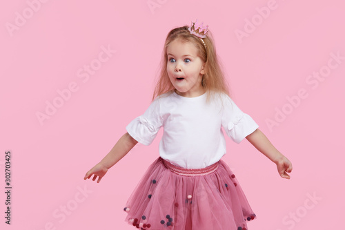 Fototapeta  A cheerful little girl with in a tulle skirt and princess crown on her head isolated on a pink background
