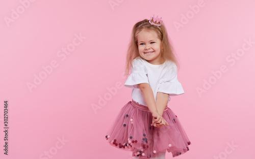 Wesoła dziewczynka w tiulowej spódnicy i księżniczce na głowie na różowym tle. Świętuje tętniący życiem karnawał dla dzieci, przyjęcie urodzinowe, dobrą zabawę