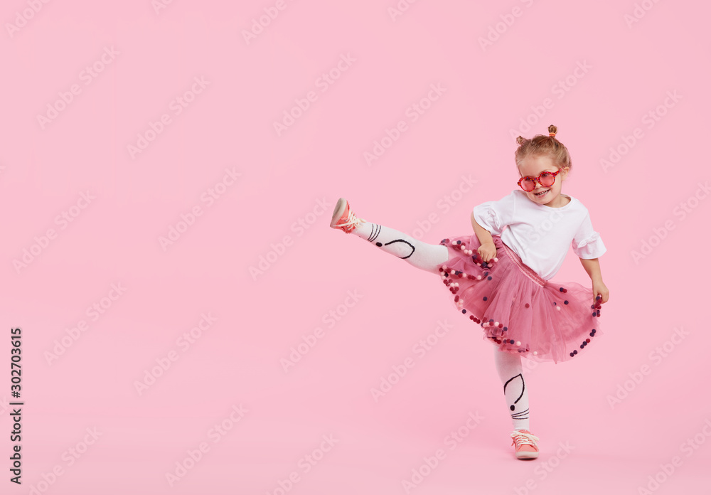 Fototapeta Happy childhood. Funny child girl in tulle skirt jumping and having fun isolated on pink background. Celebrating a vibrant carnival for kids, birthday party. True emotions. Space for text